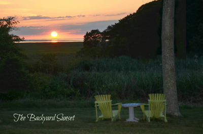 View of sunset over cape cod marsh with yellow adirondack chairs in foreground