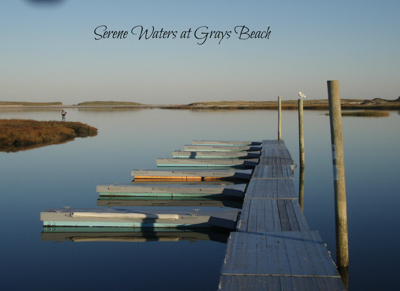 Serene waters at Grays beach. View looking down dock with several small boats.