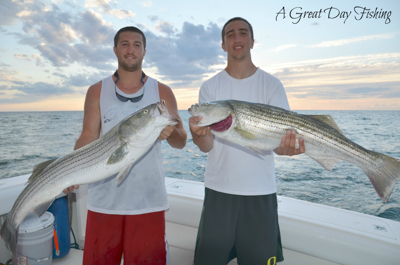 A great day fishing: two boaters pose for a photo holding large fish with ocean in background.