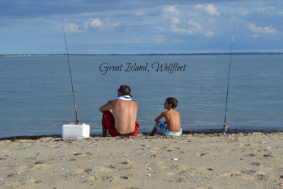 Great Island, Welfleet: A man and a boy sit on the beach beside their fishing poles looking out at ocean.